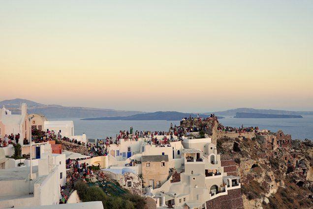 V mestu Oia se ob sončnem zahodu na strehah in modro-belih terasah zberejo množice ljudi.