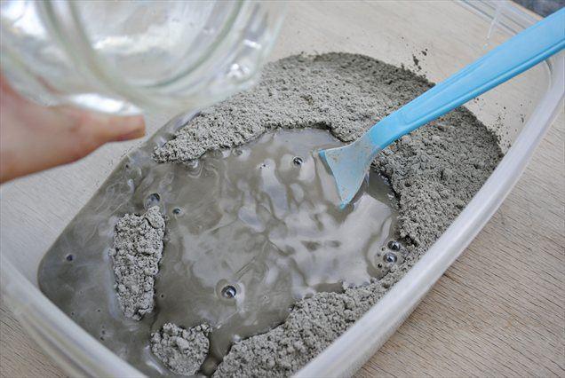 V posodo stresemo cementni prah in počasi dolivamo vodo.