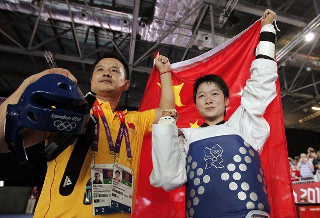 Kitajka Wu Jingyu se s trenerjem veseli novega olimpijskega naslova.